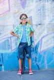 Gullig pojke med skateboarden utomhus och att stå på gatan med olika färgrika grafitti på väggarna Arkivbilder