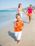 Gullig pojke med systern och modern på stranden Royaltyfri Foto