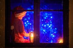 Gullig pojke och att sitta på en fönstersköld som spelar på mobiltelefonen på Arkivfoto