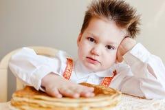 Gullig pojke och en platta av pannkakor royaltyfria bilder