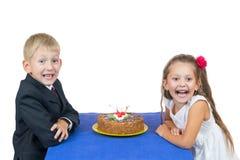 Gullig pojke och flicka med den körsbärsröda tårtan Arkivfoton