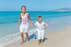 Gullig pojke och flicka på stranden Arkivfoto