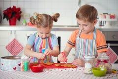 Gullig pojke och flicka som hemma förbereder julkakor arkivbild