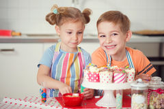 Gullig pojke och flicka som hemma förbereder julkakor royaltyfri fotografi