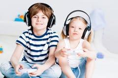 Gullig pojke och flicka som spelar dobbelkonsolen Royaltyfri Fotografi