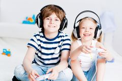 Gullig pojke och flicka som spelar dobbelkonsolen Arkivfoton