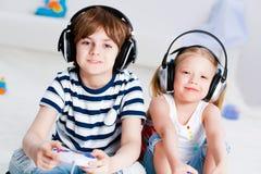 Gullig pojke och flicka som spelar dobbelkonsolen Fotografering för Bildbyråer