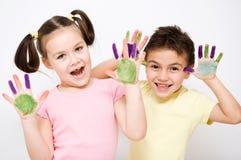 Gullig pojke och flicka som spelar med målarfärger Arkivfoto
