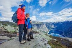 Gullig pojke och hans moder med att fotvandra utrustning i bergen Royaltyfria Foton