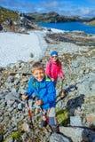 Gullig pojke och hans syster med att fotvandra utrustning i bergen Arkivbilder