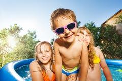Gullig pojke och två flickor som har gyckel i simbassäng royaltyfri foto