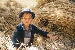 Gullig pojke på en höstferie i byn Pojken annonserar kläder för barn` s för hösten Glad grabb med a royaltyfria foton