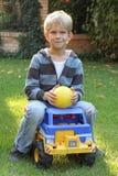 Gullig pojke på en toylastbil Arkivbild