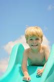 Gullig pojke på glidbana Arkivbild