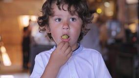 Gullig pojke som äter chokladgodisen på konfekt arkivfilmer