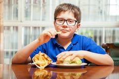Gullig pojke som äter snabbmat fotografering för bildbyråer