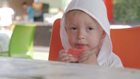 Gullig pojke som äter vattenmelon i kafé på stranden arkivfilmer