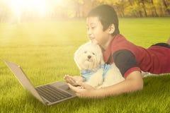 Gullig pojke som använder bärbara datorn med hans valp på parkera Fotografering för Bildbyråer
