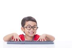Gullig pojke som använder ett tangentbord Royaltyfri Fotografi