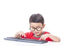 Gullig pojke som använder ett tangentbord Arkivfoto