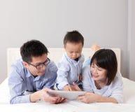 Gullig pojke som använder tabletPC med den lyckliga familjen Arkivbild