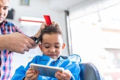 Gullig pojke som får ett hårsnitt i en Barber Shop pärlor för blå för begrepp för bakgrundsskönhet blir grund naturliga over för  arkivfoto