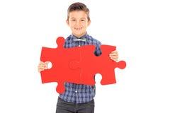 Gullig pojke som förbinder två stycken av ett pussel Arkivfoto