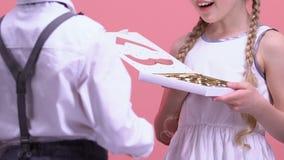 Gullig pojke som framlägger godisar till hans förvånade flickvän, valentindaggåva lager videofilmer