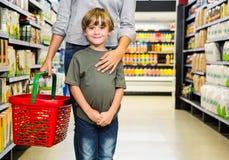 Gullig pojke som gör livsmedelsbutikshopping med modern Royaltyfria Bilder