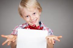 Gullig pojke som ger en gåva Arkivfoto