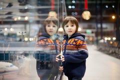 Gullig pojke som håller ögonen på några leksaker på flygplatsen, medan vänta på H royaltyfri fotografi