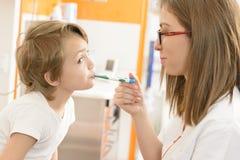 Gullig pojke som kontrolleras på kliniken Arkivfoto