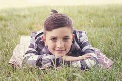 Gullig pojke som kopplar av på äng arkivbild