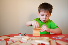 Gullig pojke som leker med träsatsen Royaltyfri Foto