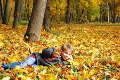 Gullig pojke som ligger på gula sidor, höstbegrepp Royaltyfri Bild