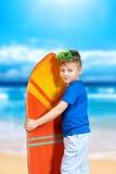 Gullig pojke som poserar med surfingbrädan royaltyfria foton