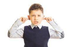 Gullig pojke som sätter hans fingrar i öron Royaltyfri Foto