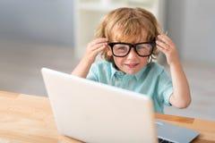 Gullig pojke som sätter på exponeringsglas Fotografering för Bildbyråer