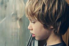 Gullig pojke som ser till och med fönstret Arkivbild