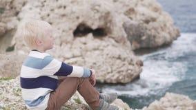 Gullig pojke som sitter på stranden och ser in i avståndet arkivfilmer