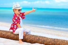 Gullig pojke som spelar en gangster på sommarstranden arkivfoton