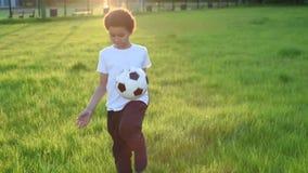 Gullig pojke som spelar fotboll med fotbollbollen på solnedgången i parkera S arkivfilmer
