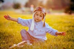Gullig pojke som spelar med flygplanet på solnedgång i parkera Royaltyfri Bild