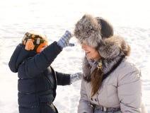 Gullig pojke som spelar med hans moder i snön Arkivfoton