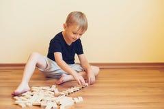 Gullig pojke som spelar på ett golv med träkvarter Framkallande leksaker Fotografering för Bildbyråer