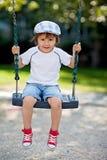 Gullig pojke som svänger på lekplatsen Royaltyfri Bild