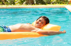 Gullig pojke som svävar på luftmadrassen i simbassäng royaltyfria bilder