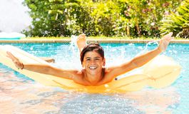 Gullig pojke som tycker om sommartid i simbassäng fotografering för bildbyråer