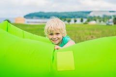 Gullig pojke som vilar på en luftsoffa i parkera Arkivbild