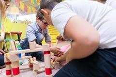 Gullig pojkebyggnad med uppmärksamhet och patiens en trästruktur royaltyfri bild